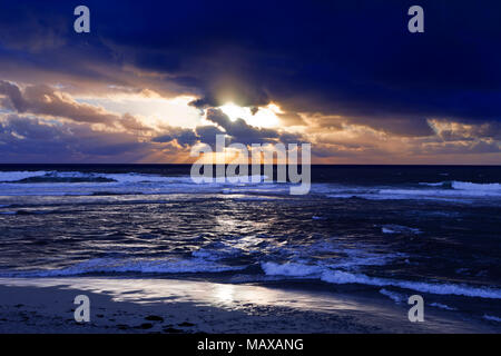 Sea scape with waves and dramatic dark clouds with a shaft  of sun rays during sunset - Stock Photo