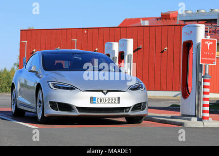 TOIJALA, FINLAND - SEPTEMBER 24, 2017: Silver Tesla Model S electric car of the updated or facelift look plugged in at Supercharger station on a beaut - Stock Photo