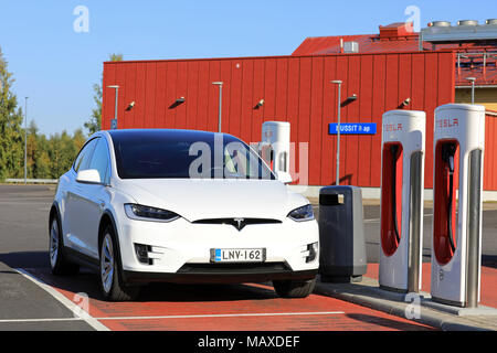 TOIJALA, FINLAND - SEPTEMBER 24, 2017: White Tesla Model X electric SUV  plugged in at Supercharger station. - Stock Photo