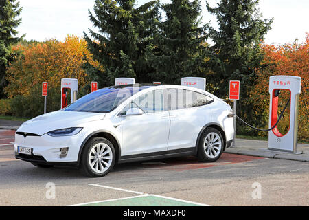 PAIMIO, FINLAND - OCTOBER 15, 2017: White Tesla Model X electric crossover SUV charges battery at Tesla Supercharger station in Paimio. - Stock Photo