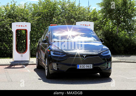 PAIMIO, FINLAND - JULY 14, 2017: Front view of black Tesla Model X SUV charging battery on Supercharger station, with in-camera reflections of the sun - Stock Photo