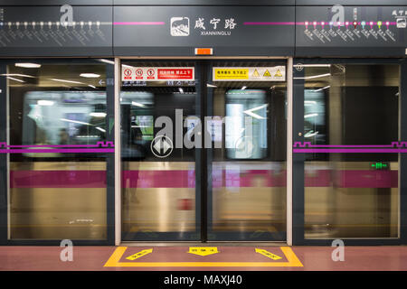 Xian Ning Lu Station with Passing Train Closed Doors in Xi'an, China, March 2018 - Stock Photo