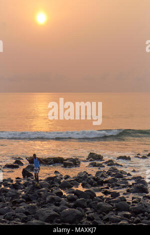 A Fisherman in Sao Tome Island with a fish at Dawn on one January Day, with the hazy sun beginning to rise in the background. - Stock Photo