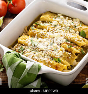 Chicken enchiladas baked with cheese in a casserole dish - Stock Photo