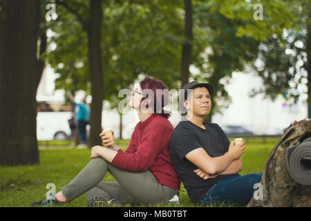 Two happy hikers eating ice cream in the summer park - Stock Photo