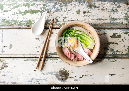 Asian dish udon noodles with egg yolk, sesame, mushrooms, boc choy, sliced sous vide cooked meat served in ceramic bowl with spoon and chopsticks over - Stock Photo