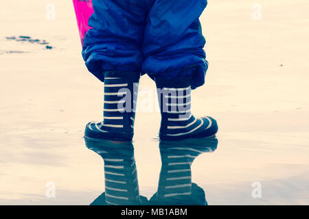 Child in a puddle of water wearing welly boots - Stock Photo