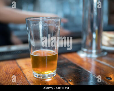 Almost empty pint glass of beer sitting on wooden bar for last call - Stock Photo
