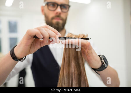 Cropped portrait of hairdresser combing client hair - Stock Photo