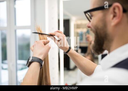 Portrait of happy hairdresser combing customer hair strand - Stock Photo