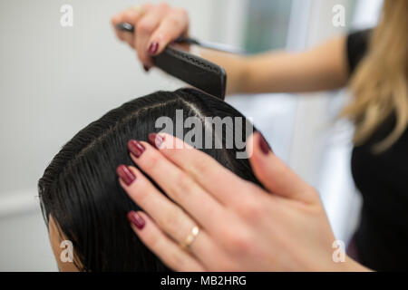 Cropped portrait of hairdresser hands combing customer hair - Stock Photo