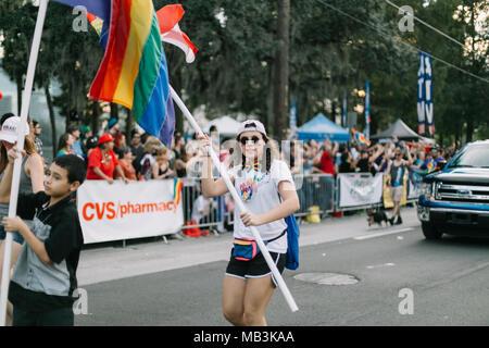Woman wearing 'Make American Gay Again' T-Shirt and holding rainbow flag at Orlando Pride Parade (2016). - Stock Photo