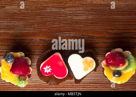 four small delicious fruit cakes , heart shape, on the wood background - Stock Photo