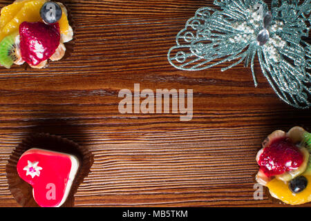 small delicious fruit cakes heart shape cake on the wood background decorated with silver butterfly - Stock Photo