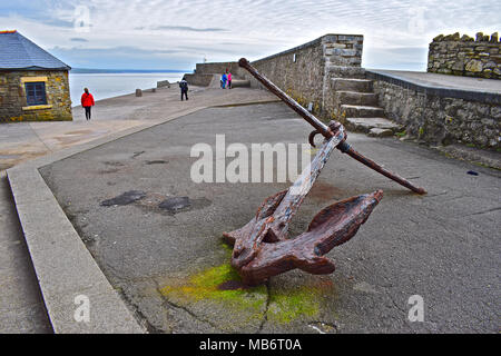 Old anchor with people strolling behind the high solid stone wall which forms the Porthcawl Harbour breakwater with the iconic lighthouse in distance. - Stock Photo