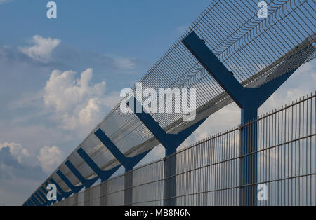 close up picture of cage fence against blue sky - Stock Photo