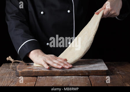 Chef kneading dough, Making dough by female hands at bakery on a black background - Stock Photo