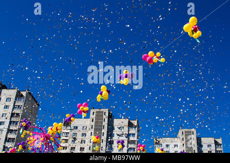 Colorful multicolored inflatable balls fly in air against background of trees and blue sky during festive festival. Salute in sky from colorful balloo - Stock Photo