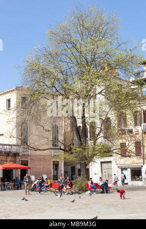 Campo San Polo, San Polo, Venice, Veneto, Italy in spring with Venetian families and their children enjoying the spring sunshine on colorful red bench - Stock Photo
