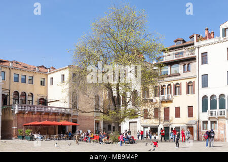 Campo San Polo, San Polo, Venice, Veneto, Italy in spring with locals and their kids enjoying the sunshine and relaxing on benches under trees - Stock Photo