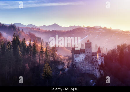 Bran or Dracula Castle in Transylvania, Romania. The castle is located on top of a mountain, sunset light - Stock Photo