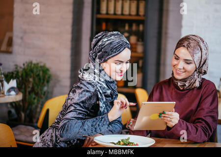 Two Muslim women in cafe, shop online using electronic tablet - Stock Photo