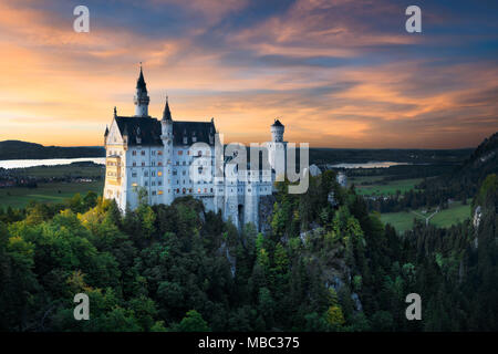 Beautiful view of world-famous Neuschwanstein Castle. Colorful sky during sunset. Autumn colors of forest. Scenic mountain landscape near Fussen, sout - Stock Photo