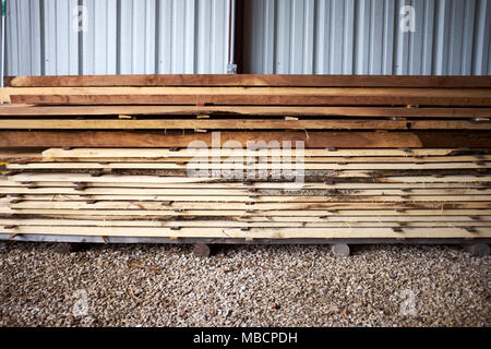 Freshly cut or milled rough lumber planks neatly stacked in a yard at a timber mill outside a metal wall of a warehouse - Stock Photo