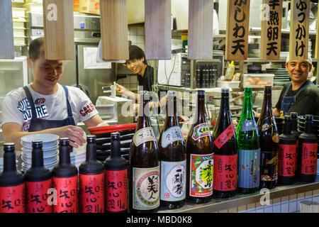 Tokyo Japan Akihabara Asian man men workers restaurant kitchen cook kanji hiragana katakana characters symbols Japanese English - Stock Photo