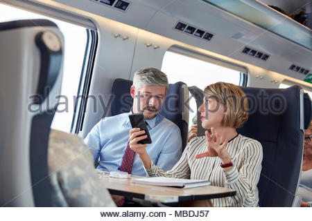 Business people working, using smart phone and talking on passenger train - Stock Photo