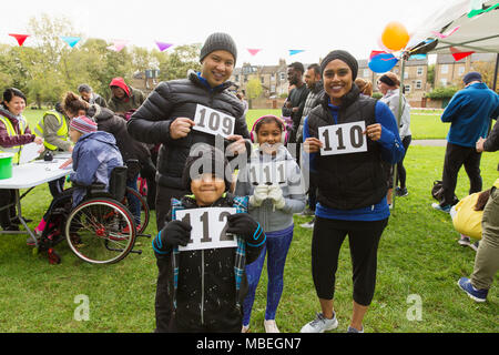 Portrait confident family runners showing marathon bibs at charity run in park - Stock Photo
