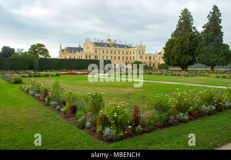 Chateau park Lednice with flowers and trees. On the left is Lednice castle. - Stock Photo