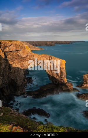 Seaside cliff arch, one of the sought after famous seaside destination. cliff, ocean with splashing water on a sunny day - Stock Photo