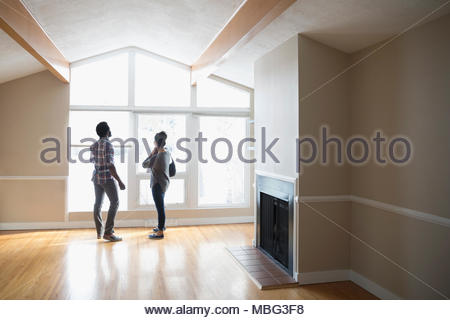 Young couple at window shopping for new house - Stock Photo