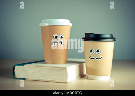 Two cute takeaway coffee cups and book. - Stock Photo