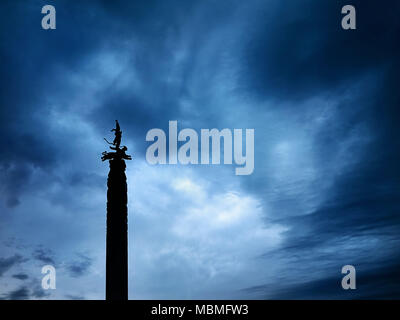 Silhouette of statue with warrior on leopard is Independence Monument on Republic Square of Almaty in Kazakhstan at dark cloudy sky background - Stock Photo