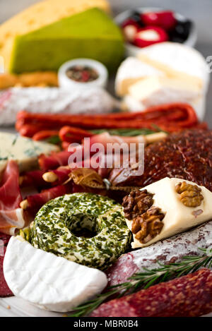 Traditional italian antipasto, cutting board with salami, cold smoked meat, prosciutto, ham, cheeses, olives, capers on grey background. Cheese and meat appetizer. - Stock Photo
