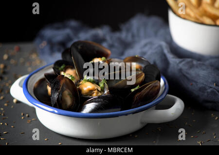 moules-frites, mussels and fries typical of Belgium, on a rustic wooden table - Stock Photo