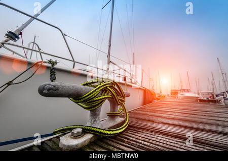 yacht moored in a marina, close up of metal cleat and ropes mooring the boat - Stock Photo