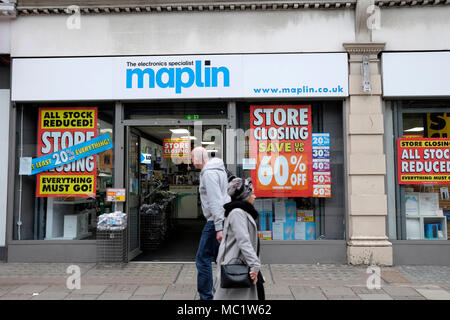 Two people walk past Maplin shop on Tottenham Court Road, central London, UK - Stock Photo
