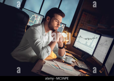 Focused thoughtful trader or serious investor working at night overtime analyzing stock trading graphs looking at computer monitors controlling market - Stock Photo