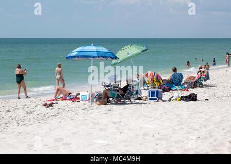 Vacationers in Naples, Florida enjoying beach activities. Sunbathing and having fun on the beach. - Stock Photo