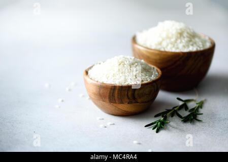 White raw organic jasmine rice in wooden bowl and rosemary on light concrete background. Food ingredients. Copy space - Stock Photo