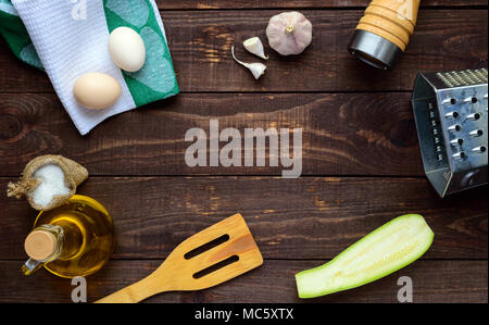 The ingredients and tools for cooking pancakes from zucchini  on a dark wooden background. top view. In the middle of the free space for text - Stock Photo