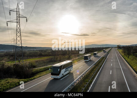 Caravan or convoy of busses in line on a country highway - Stock Photo