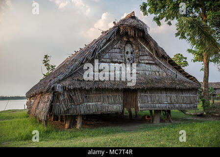 Haus Tambaran (men's or spirits house) decorated with a wood carved mask, Kaminibit village, East Sepik Province, Papua New Guinea - Stock Photo