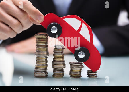 Close-up Of A Businessman's Hand Holding Red Car Over Stacked Coins Over Desk - Stock Photo