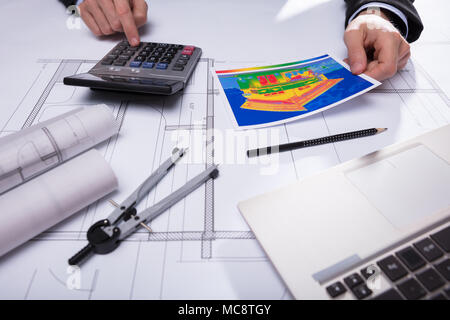 Close-up Of Architecture's Hand Using Calculator While Holding Home Thermal Heat Loss - Stock Photo