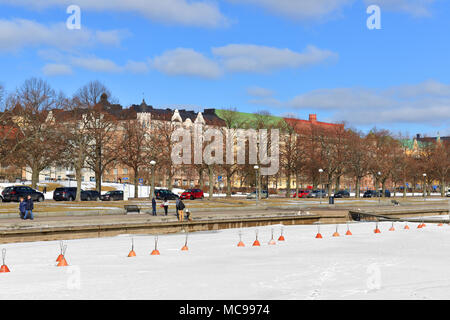 Residents of city and tourists walk along embankment in early spring - Stock Photo