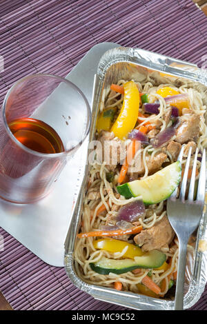 Chinese takeaway of Chicken noodle stir fry in a foil delivery dish with a glass of Saki - Stock Photo